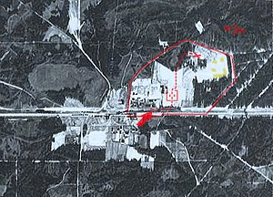 "Sobibór extermination camp - Aerial photograph of the Sobibór perimeter. taken likely before 1942. Permanent structures are not there yet, including Camp II barracks (lower centre), Camp III, and Camp IV. The railway unloading platform (with visible prewar railway station) is marked with the red arrow; the location of gas chambers is marked with a cross. The undressing area, with adjacent ""Road to Heaven"" through the forest, is marked with a red square."