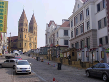 A street with Saint Michael's Cathedral rising in the distance. Cars are parked along one side of the street, and a row of four story buildings stand along the other side.