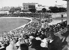 A crowd watching a cricket match