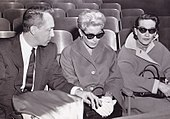 Two women wearing sunglasses seated next to a man