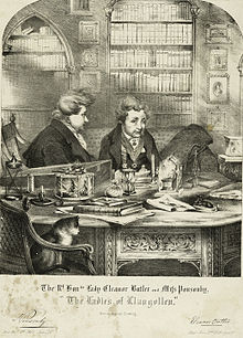 "An engraved drawing of Eleanor Butler and Sarah Ponsonby, known as the ""Ladies of Llangollen"". They are shown sitting in a private library wearing smoking jackets, with a cat in the foreground sitting in a chair."