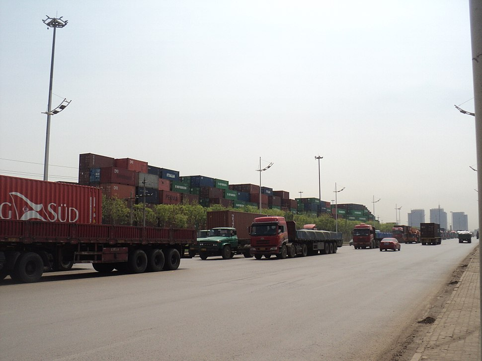 line of heavy trucks going north, background a container yard