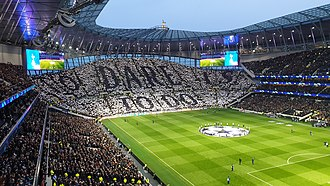 Fans displaying the club motto 'To Dare Is to Do' on the South Stand before the UEFA Champions League quarter-final with Manchester City on 9 April 2019. Tottenham Hotspur Stadium South Stand.jpg