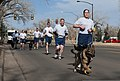 U.S. Air Force Staff Sgt. Adrienne Dunham, foreground, a military working dog handler assigned to the 90th Security Forces Squadron, and her dog, Hugo, take part in a 90th Security Forces Group pride run 130329-F-JW079-094.jpg