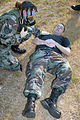 U.S. Air Force Staff Sgt. Megan Harper, wearing a gas mask, assists Master Sgt. Tracy Sisco, after he pretended to be struck by a simulated chemical explosive device during a ROCKEX exercise at Little Rock Air 070815-F-YN203-001.jpg