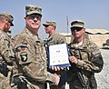 U.S. Army Brig. Gen. Duane Gamble, second from left, the deputy commanding general of the 1st Sustainment Command, awards a Combat Action Badge to Spc. Brandon J. Burns, with the 864th Engineer Battalion 131007-A-WQ129-007.jpg