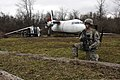 U.S. Army Pfc. Aubrey Russell, with a site security team, Charlie Company, Task Force Raptor, provides security while his team searches a downed aircraft for sensitive items during a training scenario at Camp 120119-A-FG822-015.jpg