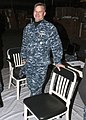 U.S. Navy Capt. Randall Peck, the executive officer for the aircraft carrier USS Abraham Lincoln (CVN 72), poses for a photo with one of the chairs to be used in refitting the ship in Newport News, Va., Dec. 11 131211-N-EB301-072.jpg