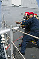 U.S. Navy Culinary Specialist 1st Class Eber Barraza provides fire hose training during a drill aboard the guided missile cruiser USS Philippine Sea (CG 58) in the Arabian Sea April 5, 2014 140405-N-PJ969-257.jpg