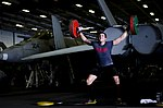 U.S. Navy Mass Communication Specialist 2nd Class Trevor Welsh lifts weights in the hangar bay of the aircraft carrier USS George Washington (CVN 73) in the Coral Sea Aug. 8, 2013 130808-N-BD107-080.jpg