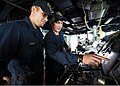 U.S. Navy Seaman Patrick David, right, trains Seaman Bronson Bebee on the duties of a master helmsman in the pilot house aboard the guided missile destroyer USS Mustin (DDG 89) Nov. 4, 2013, in the South China 131104-N-CG241-061.jpg