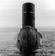 Large submarine surface displaying its bow, upper deck, and large conning tower.