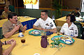 US Navy 030331-N-4843P-002 Master Chief Petty Officer of the Navy (MCPON) Terry Scott speaks with Hospital Corpsman 1st Class Joseph Speranza and Hospital Corpsman 1s Class Tessie Delossantos while having lunch with Sailors in.jpg