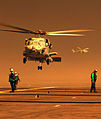 US Navy 031026-N-4768W-868 An HH-60H Seahawk takes off from the flight deck of USS John C. Stennis (CVN 74) as an SH-60F Seahawk prepares to land under smoke-filled skies from nearby San Diego County firestorms.jpg