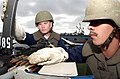 US Navy 040928-N-8158F-133 Aviation Ordnanceman 3rd Class Charles Wilker of Fowler, Calif., left and Aviation Ordnanceman 3rd Class Allen Ortega of Winnemucca, Nev., practice loading drills on a .50 caliber machine gun.jpg