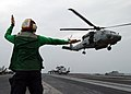 US Navy 050120-N-4308O-004 Aviation Electrician's Mate 3rd Class Megan Truncer, a Landing Signal Enlisted (LSE), signals the pilot of an SH-60F Seahawk that he is clear to lift away.jpg