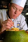 US Navy 070404-N-7780S-003 Culinary Specialist Seaman Travis Rhinehart carefully carves a food serving line showpiece out of a watermelon for the afternoon meal.jpg