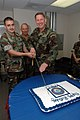 US Navy 071010-N-2456S-081 Information Systems Technician Seaman Bradley Encinas and Capt. Jeff McKenzie, commanding officer of Expeditionary Combat Readiness Command (ECRC), cut the cake as the youngest and oldest members of E.jpg