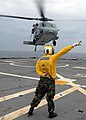 US Navy 080212-N-5067K-247 Aviation Boatswains Mate (Helicopters) Airman, Kevin A. Bourne directs an MH-60S Seahawk after take-off from the flight deck of the amphibious transport dock USS Juneau (LPD 10) during deck landing qu.jpg