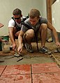 US Navy 100120-N-8463W-100 Africa Partnership Station (APS) East Sailors, Lt. j.g. Brent Southerland, left, and Boatswain's Mate Seaman Aaron Kazol, lay floor tiles at the Kidz Care Orphanage in Dar Es Salaam, Tanzania.jpg