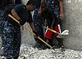 US Navy 100209-N-5244H-044 A Haitian boy helps Information Systems Technician 2nd Class Shaunte Stafford remove rubble.jpg