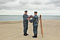 US Navy 110603-N-AL752-089 Construction Electrician 2nd Class Jeremy Keller presents a wreath to Cmdr. William Rabchenia during a wreath-laying cer.jpg