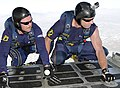 US Navy 110702-N-OU681-086 SEALs assigned to the U.S. Navy parachute demonstration team, the Leap Frogs, hold onto the ramp of a C-130 cargo aircr.jpg