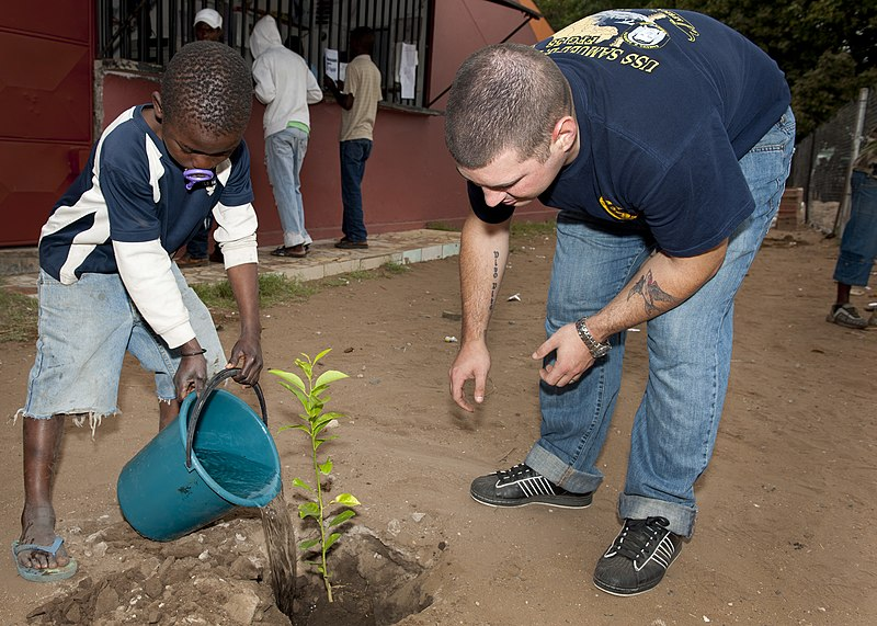 File:US Navy 110827-N-OV802-050 Information Systems Technician 1st Class Kenneth Pirches helps a student water a newly planted tree during a community s.jpg