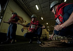 US Navy 120202-N-DR144-123 Line handlers take in a line in the hangar bay aboard the Nimitz-class aircraft carrier USS Carl Vinson (CVN 70) as the.jpg