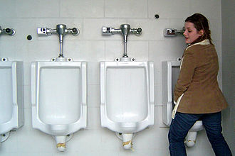 Female urination device - Woman using the Urinella, a type of female urination device, to adapt to standard men's room urinals
