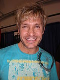 A man in a light blue t-shirt smiles towards the camera.  He has blond tousled hair, and sports a stubble.