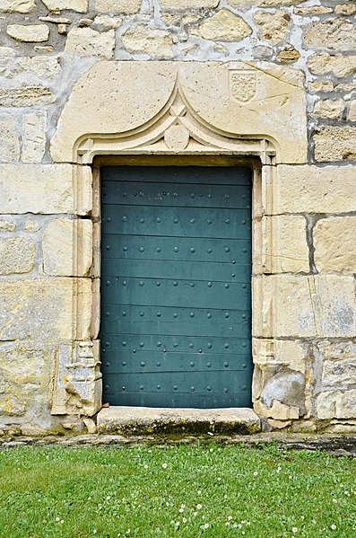 Lateral entrance (probably 16th century) of the church, with hammered COA, Vitrac-Saint-Vincent, Charente,France.