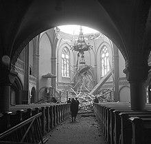 La cúpula de la catedral de Vyborg se derrumbó tras el bombardeo soviético.  Cuatro personas se paran en la nave y miran los escombros, resaltados por la luz del sol que brilla a través de la cúpula dañada.
