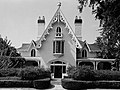 A black and white photograph of a house with steeply roofed gables. Gingerbread molding frames the gables, whose ends contain windows with rounded tops.