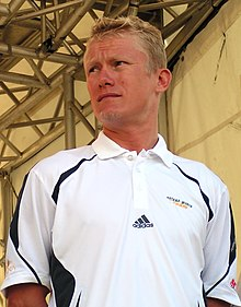 A blond-haired man in his mid-thirties, wearing a white polo shirt bearing an Adidas logo. He is looking to his right.