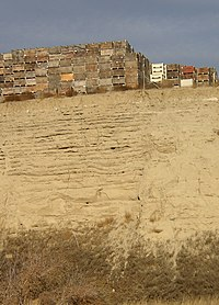 This photo shows a canyon cut into the surrounding flat soil with over 20 distinct horizontal layers of sediment, each clearly demarked from the layer below. Above the canyon lip a number of boxes used for transporting harvested apples are stacked; the size of these boxes indicates that the layers each are 0.5–1 meter in depth.