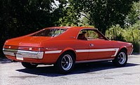 Shows the rear right of a 1969 AMC Javelin SST finished in red with white bodyside C-stripe