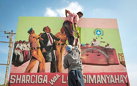 "A billboard mural saying ""Before the law, all people are equal"" fixed into place by a cooperative of artists along the approach road to Mogadishu International Airport 2013 01 15 Somali Artists Shoot II d (8404019559).jpg"