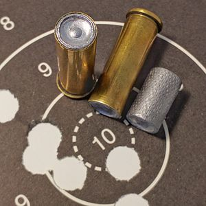 Wadcutter - .38 Special wadcutters loaded cartridges, 148 grain hollow-base wadcutter bullet and target showing the clean round holes.