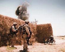Marines accanto a un muro di fango in un'esplosione si spegne alle spalle