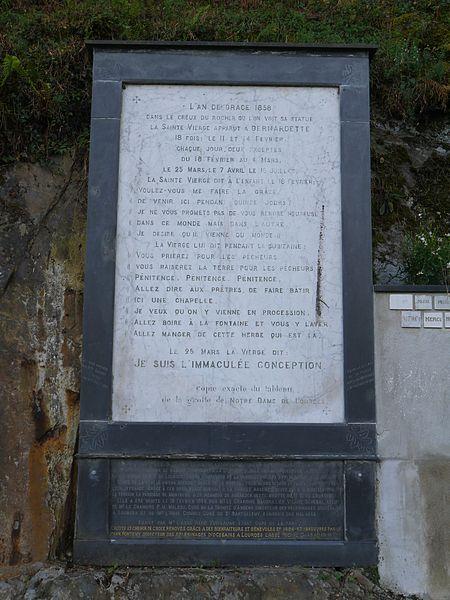 Pierre résumant les apparitions de Lourdes, à gauche de la grotte.