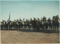 Amir Abdullah's Bodyguard on Camels with Red, Green and White Standard at Far Left.png