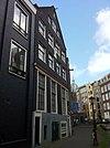 foto van Huis met gevel waarin fraaie gesneden puibalk en wapensteen waarop DE LEUPART en 18C