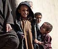 An Afghan boy smiles for the camera while waiting to receive aid from Romanian Army Soldiers from 300th Mechanized Infantry Battalion, St. Andrew, 2nd Infantry Company, stationed at Patrol Base 19 and officers 120111-A-FZ921-226.jpg