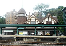 A view of an ornate structure with railroad tracks and a modern elevated platform and metallic structure in the foreground