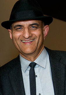 Ashraf Habibullah wearing hat, jacket, and tie.jpg