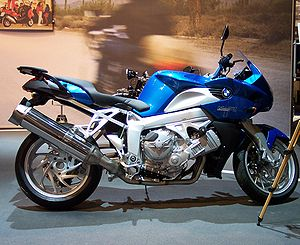 Blue BMW K1200R indoors with a promotional display in the background