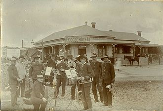 Coogee Hotel, Western Australia - A group of men in uniforms stand in front of the Coogee Hotel holding instruments.