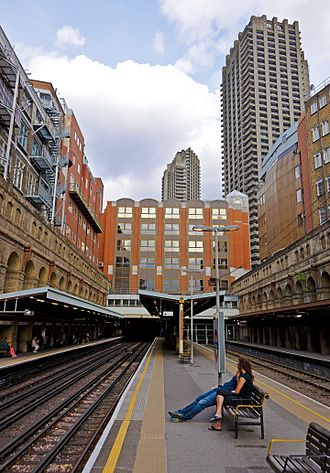 Barbican tube station - View of Barbican station platforms, with the Barbican Estate towers in the background, 2014