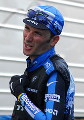 A man in his early thirties, wearing a black and white cycling jersey with blue trim. He also wears a matching cap, with a pair of sunglasses on the cap
